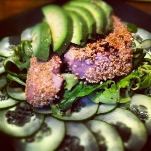 Sesame crusted Tuna over cucmber and arugula topped with avocado